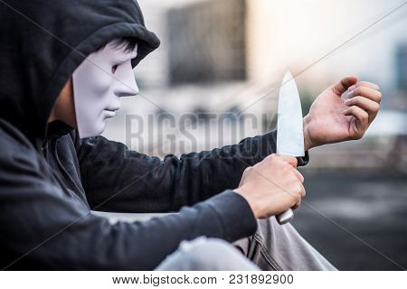 Mystery Man In The White Mask Putting A Knife On His Wrist Considering Suicide, Depression Self Dest