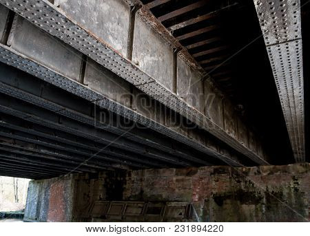 The Weathered Steel Beams Of The Bridge Over The Canal