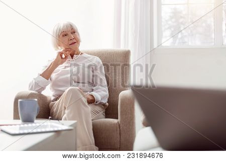 Attentive Listener. Petite Senior Woman Sitting In An Armchair In The Living Room And Looking Away F
