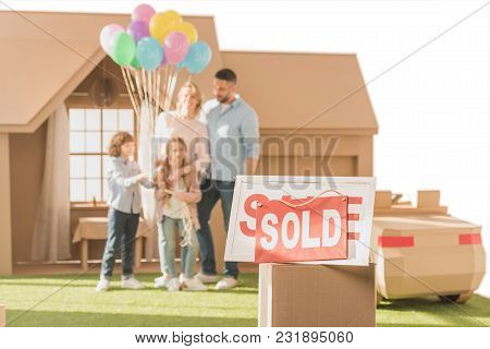 Sold Signboard With Young Family On Yard Of Their New Cardbord House Blurred On Background Isolated