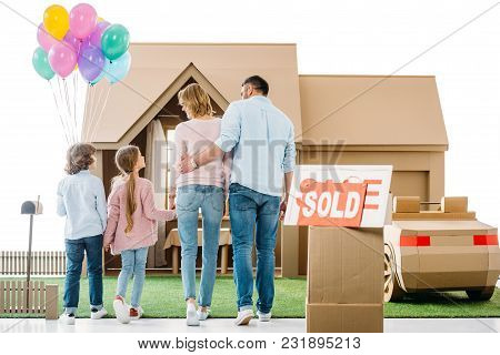 Back View Of Young Family Moving Into New Cardbord House Isolated On White
