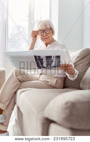 Gripping Content. Pleasant Elderly Lady Sitting On The Couch And Reading An Interesting Newspaper Wh