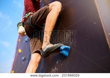 Rock Climber About To Start Climbing His Route, Bottom View With His Foot On The Foreground