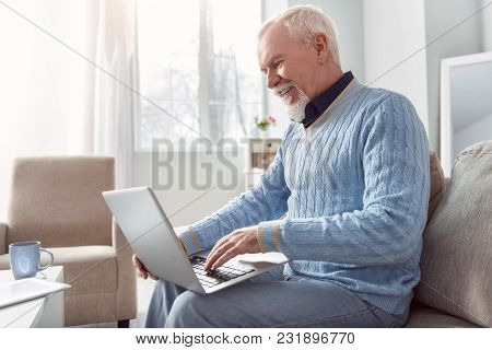 Mood-boosting Chat. Upbeat Senior Man Sitting On The Couch And Typing An Email On The Laptop While S