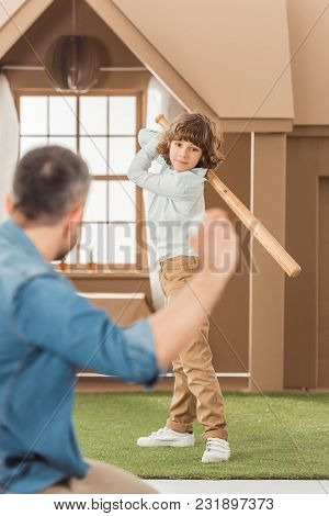 Father Teaching His Little Son How To Play Baseball In Front Of Cardboard House