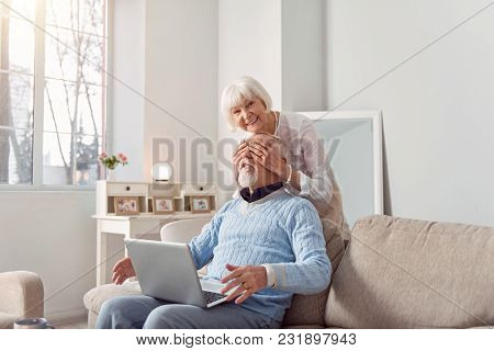 Pleasant Surprise. Charming Upbeat Senior Woman Surprising Her Husband By Covering His Eyes From Beh