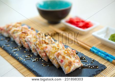 Sushi Rolls Made Of Rice, Salmon And Cream Cheese. Hot Sushi Roll On Black Slate Surface. Japanese F