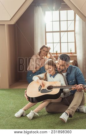 Handsome Father And Daughter Playing Guitar On Grass In Front Of Cardboard House With Mother Sitting
