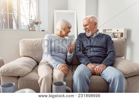 Having Fun Together. Cheerful Elderly Couple Sitting On The Couch In The Living Room And Laughing Wh