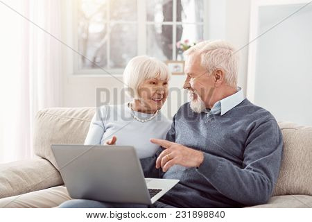 Sharing Opinions. Joyful Senior Husband And Wife Sitting On The Sofa In The Living Room And Discussi