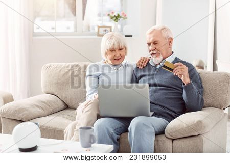 Convenient Service. Upbeat Elderly Couple Sitting On The Couch And Using Their Bank Card While Payin