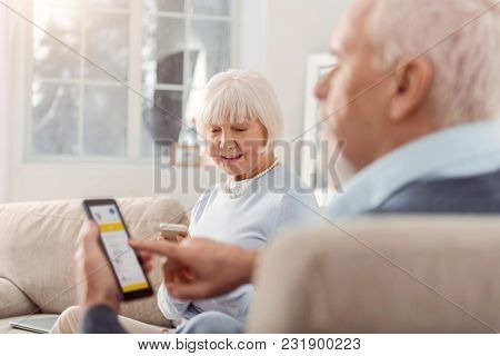Useful Technologies. Pleasant Elderly Couple Sitting In The Living Room And Being Focused On Their M
