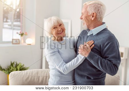 Enjoy Dancing. Happy Charming Elderly Woman Smiling At The Camera While Dancing Waltz With Her Husba