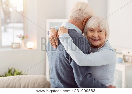 Happy Wife. Pleasant Elderly Woman Smiling At The Camera While Hugging Her Beloved Husband During Th