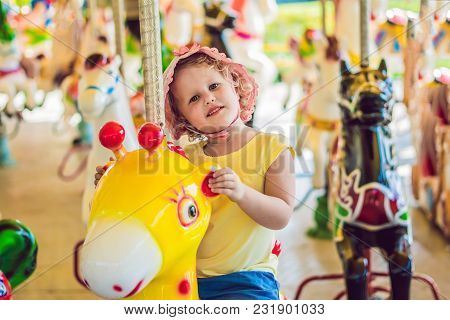 Cute Little Girl Enjoying In Funfair And Riding On Colorful Carousel House.