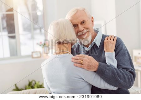 Happy Husband. Joyful Elderly Man Smiling At The Camera While Dancing With His Beloved Wife, Hugging