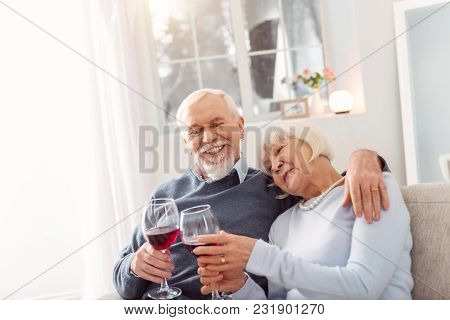 Relaxing Together. Cheerful Elderly Couple Sitting On The Couch And Cuddling While Celebrating Their