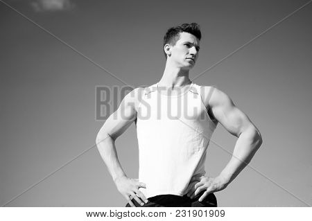 Man Bodybuilder Posing On Blue Sky. Athlete In Green Tshirt On Sunny Day. Healthy Lifestyle Concept.