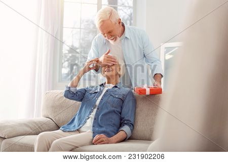 Best Gift. Charming Elderly Man Congratulating His Beloved Wife On Her Birthday And Making A Surpris