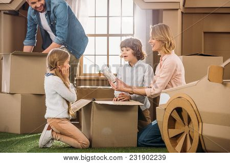Young Family Unpacking Boxes While Moving Into New Cardboard House