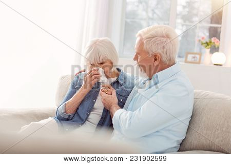 Do Not Cry. Caring Elderly Man Sitting On The Couch Next To His Wife And Trying To Cheer Her Up Whil