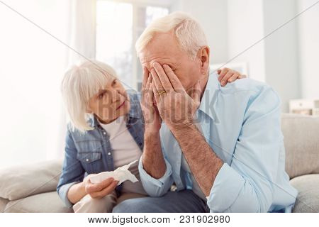Caring Wife. Petite Senior Woman Holding A Tissue And Stroking Her Husbands Back, Trying To Console