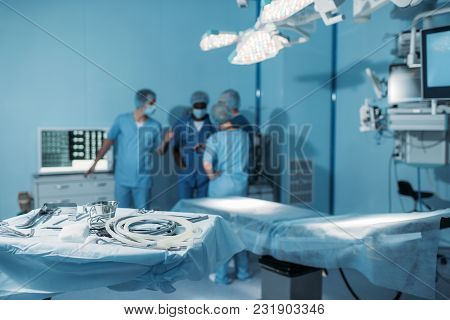 Four Multiethnic Surgeons In Operating Room With Tools On Foreground