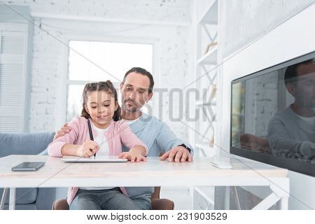 Home Lesson. Delighted Cheerful Nice Girl Sitting At The Table And Using A Tablet While Studying