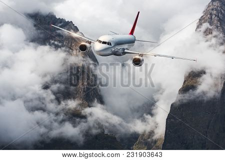Aircraft, Mountains In Overcast Sky. Airplane