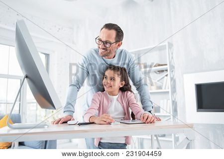 Home Teacher. Happy Positive Delighted Man Standing Behind His Daughter And Looking At The Computer