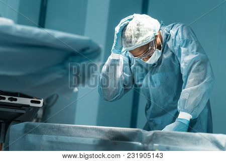 African American Surgeon Touching Head In Operating Room