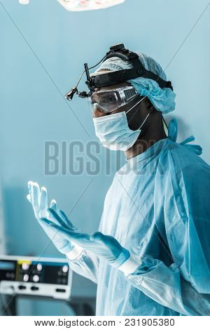 Side View Of African American Surgeon In Medical Gloves In Operating Room