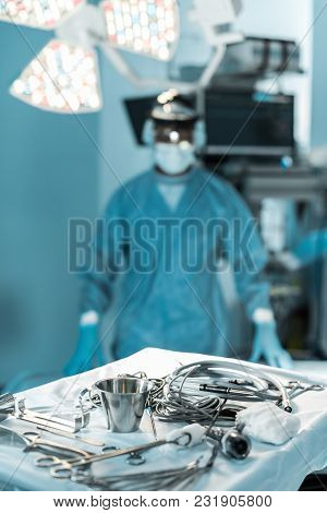 Surgeon Looking At Camera In Operating Room With Tools On Foreground