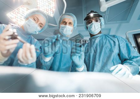 Bottom View Of Multicultural Surgeons Looking At Patient During Surgery