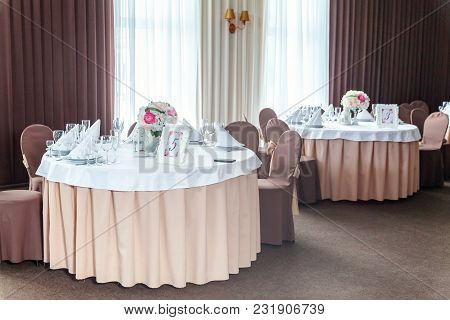 Glasses, Flowers, Fork, Knife, Napkin Folded In A Pyramid, Served For Dinner In Restaurant With Cozy