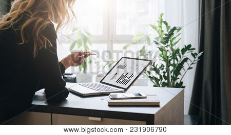 Young Businesswoman Is Standing Near Table, Pointing Pencil On Graphs, Charts, Diagrams, Schedules O