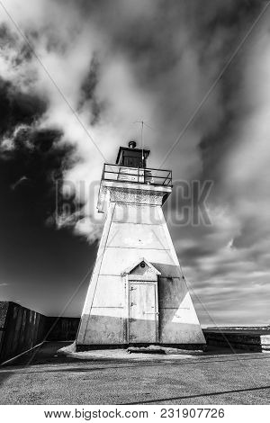 Rugged White Lighthouse Standing Tall With Dramatic Sky And Cloud Behind. Wide Angle Black And White