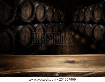Old wooden table top and oak wine barrels at the background. Wine background.