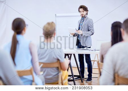 Young confident speaker with notepad standing by whiteboard while making presentation to audience at seminar