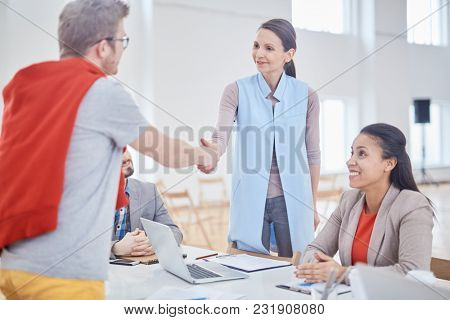 Young elegant businesswoman in smart casual shaking hand with new partner at meeting