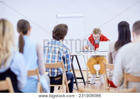 Young teacher sitting by desk in front of audience and looking through his notes before presentation