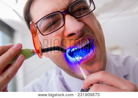 Funny dentist with curing light in medical concept