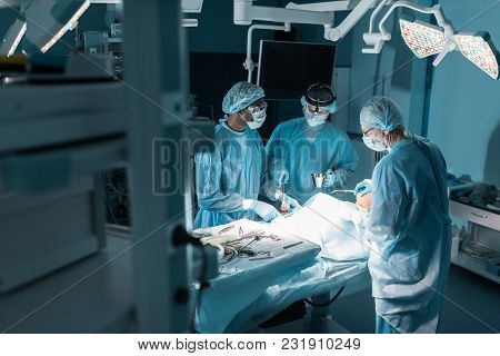 Three Multicultural Surgeons And Patient In Operating Room