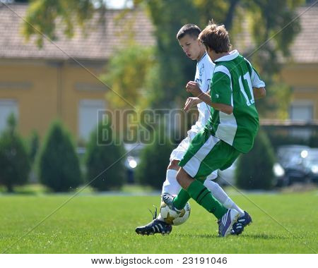 KAPOSVAR, HUNGARY - SEPTEMBER 5: Gerely Jozsef (in green) in action at the Hungarian National Championship under 19 game Kaposvar (white) vs. Nagyatad (green) September 5, 2011 in Kaposvar, Hungary.