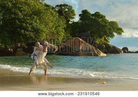 Happy Elderly Couple On Sandy Beach Near Tropical Resort