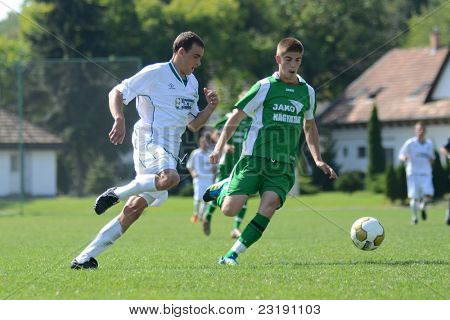 KAPOSVAR, HUNGARY - SEPTEMBER 5: Kristof Kovacs (in green) in action at the Hungarian National Championship under 19 game Kaposvar (white) vs. Nagyatad (green) September 5, 2011 in Kaposvar, Hungary.