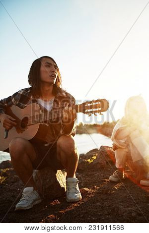 Guy with guitar sitting on stone and singing for his friends on summer evening by campfire