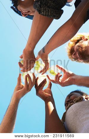 Hands of five friends holding glasses with lemonade and clinking them against blue sky