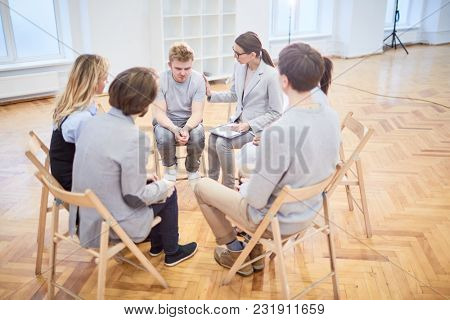Group of employees listening to story of their desperate colleague while psychologist supporting him