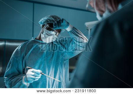 African American Surgeon Touching Forehead During Surgery